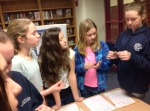 Archaeology students examine artifacts