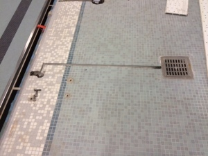 This photo shows how the tile was cut to accommodate the wiring for the new bonding.