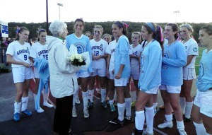 SHS Girls Soccer Team presenting white roses to Mrs. DeConto before taking the field for the first game at DeConto Stadium.