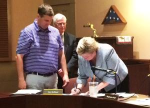 Dr. Gould, signing her contract, as Jay McGrail and Dr. Richard Canfield look on.